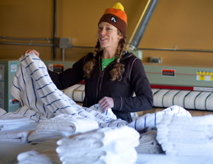 Owner, Cassie Pence folds laundry.